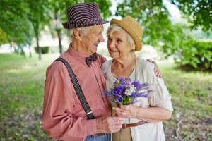 Mature lovely couple with flowers outdoors
